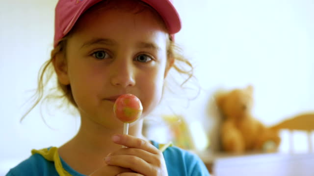 Little girl enjoying a lollipop while staring at camera. Child eating candy, sweets, sugar