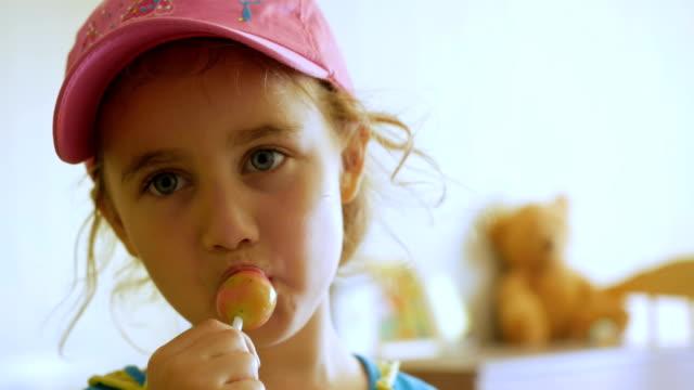 小女孩一邊欣賞棒棒糖, 一邊盯著鏡頭。吃糖果、糖果、糖的孩子 - 波板糖 個影片檔及 b 捲影像