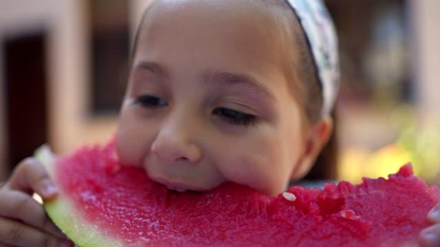 Little girl enjoying a slice of juicy watermelon Cute little girl eating a watermelon in her yard watermelon stock videos & royalty-free footage