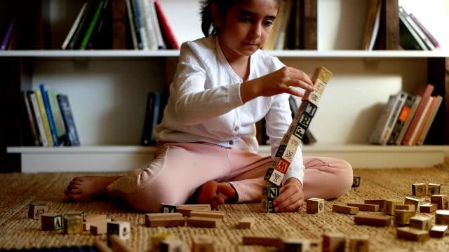 stockvideo's en b-roll-footage met langzame mot - meisje geniet van bouwen met blokken op verdieping - peuterklasleeftijd