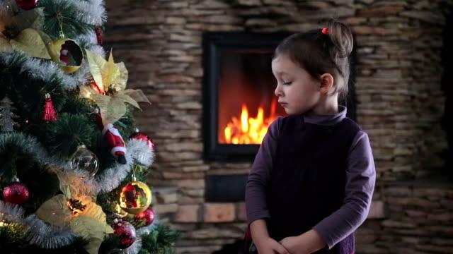stockvideo's en b-roll-footage met meisje onderzoekt de kerstboom met grote nieuwsgierigheid. - bewondering