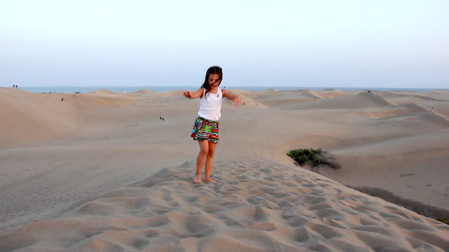 Little girl failing to do somersault at sunset in Maspalomas sand dunes, Gran Canaria