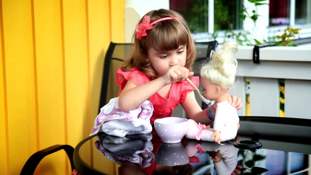 Little girl feeding a doll video