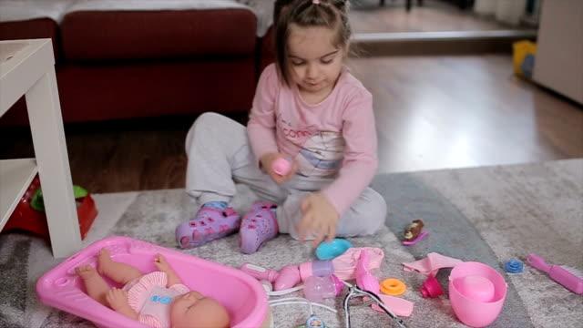 Little girl feeding his little doll friend Little girl feeding his little doll friend doll stock videos & royalty-free footage