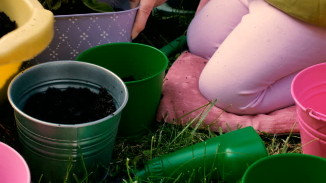 Little girl filling flower pot with soil, gardening with mother