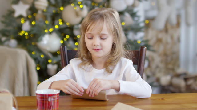 Little Girl Folding Letter to Santa into Envelope - vídeo