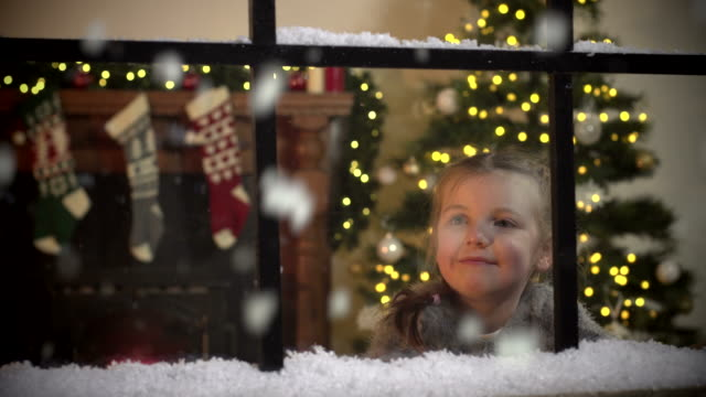 Little Girl gazing at Snow falling through window at Christmas Stock 4K video clip footage of a small child gazing in wonder at the snow falling outside the window at Christmas. The little girl is inside the house with it's Christmas Tree and Christmas stockings hung on the fireplace. She is excited at first but then gazes at the flakes falling. christmas stocking stock videos & royalty-free footage