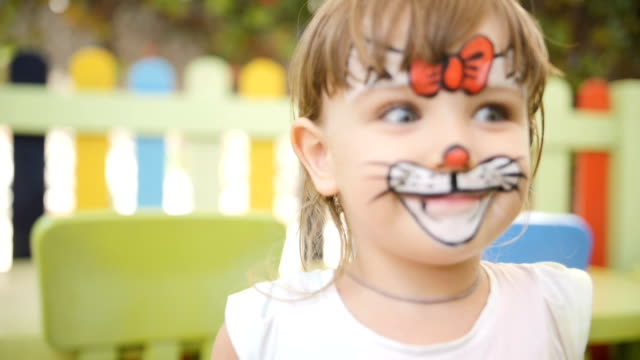 little girl get painted face as a cat for a carnival - карнавал стоковые видео и кадры b-roll
