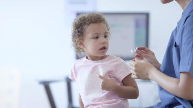 little girl getting a hearing aid - orecchio umano video stock e b–roll