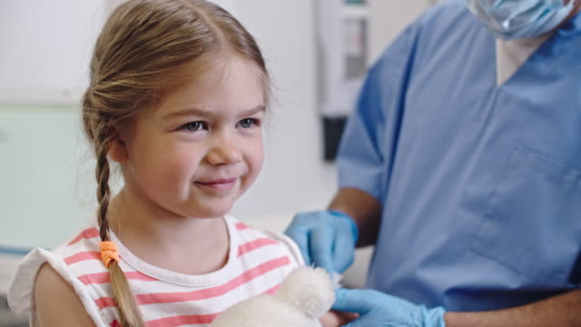 Little Girl Getting Vaccine Smiling little girl sitting at doctors appointment, then wincing when getting a shot flu shot stock videos & royalty-free footage