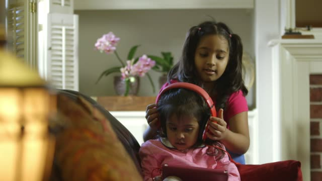 Little girl gives the headphones to her little sister video