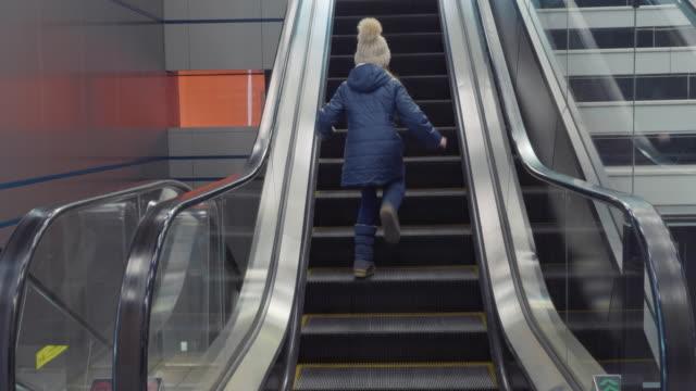 Little girl goes up the escalator.