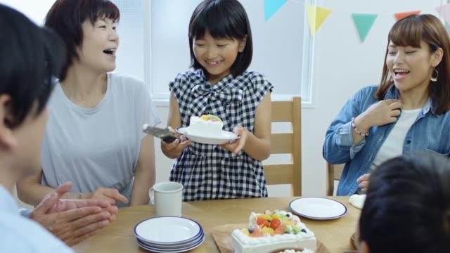 少女の家族に誕生日ケーキを配って - 家族での夕食点の映像素材/bロール
