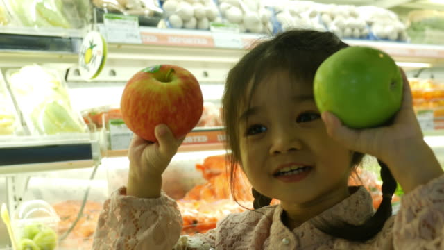 little girl having fun shopping in supermarket little girl having fun shopping in supermarket apple fruit stock videos & royalty-free footage