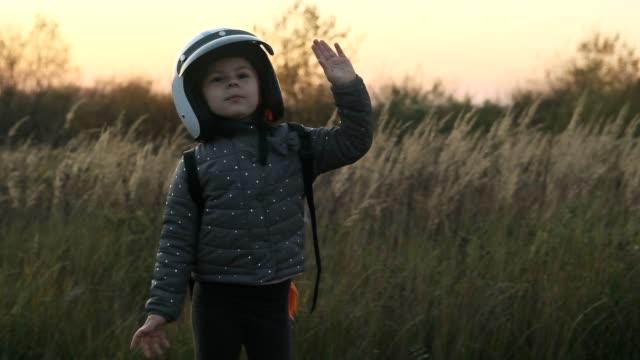 kleines mädchen mit spaß mit weißen helm und jetpack im freien in zeitlupe - raumanzug stock-videos und b-roll-filmmaterial