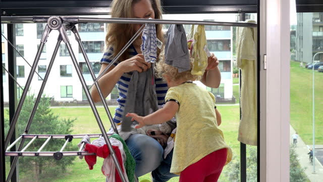 liten flicka som hjälper sin mor kvinna att hänga tvättad tvätt - förskoleelev bildbanksvideor och videomaterial från bakom kulisserna