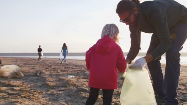 little girl helps her parents to clean up area of dirty beach with garbage bags - odzyskiwanie i przetwarzanie surowców wtórnych filmów i materiałów b-roll