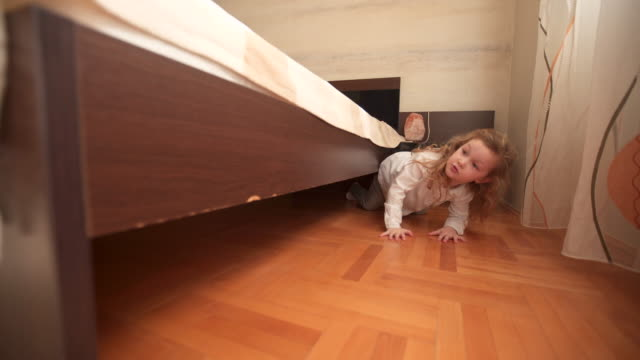 little girl hiding below bed - birichinata video stock e b–roll