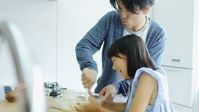 Little Girl Holding Bowl as Father Stirs Cake Batter video