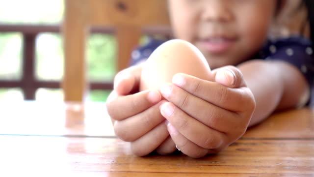 Menina, segurando o ovo na mão. Câmera de movimento é zoom em. - vídeo