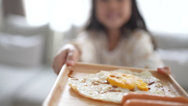 Little girl holding fried egg and sausage in breakfast