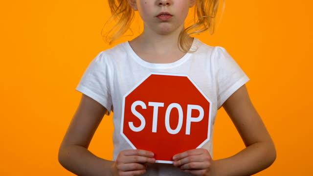 dziewczynka trzymająca szablon znaku stop w rękach, ochrona praw dzieci - negacja filmów i materiałów b-roll