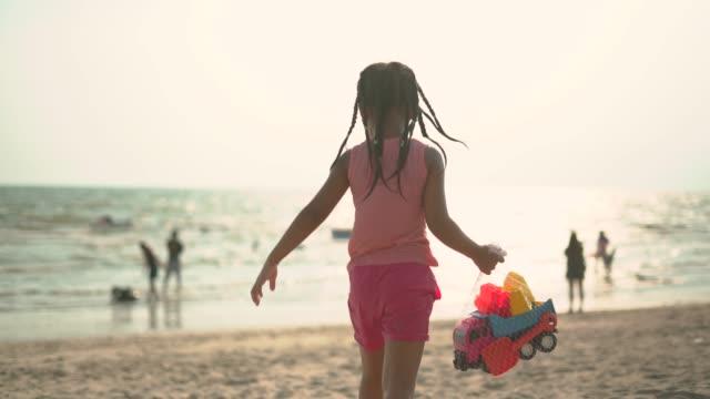 Little girl holding toy truck in her hand walking toward seashore