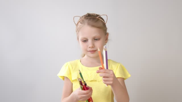 A little girl holds colored pencils in her hands. The girl is preparing to draw.