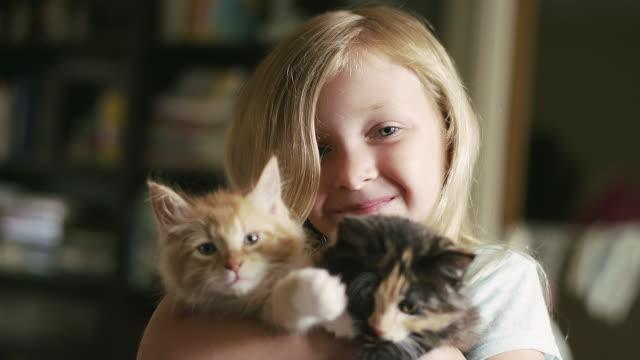 Una niña pequeña que abrazan gatitos en los dos brazos de - vídeo