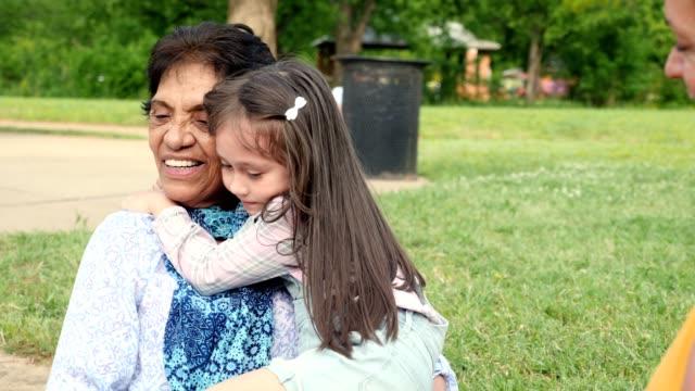 la bambina abbraccia la sua bisnonna - etnia latino americana video stock e b–roll