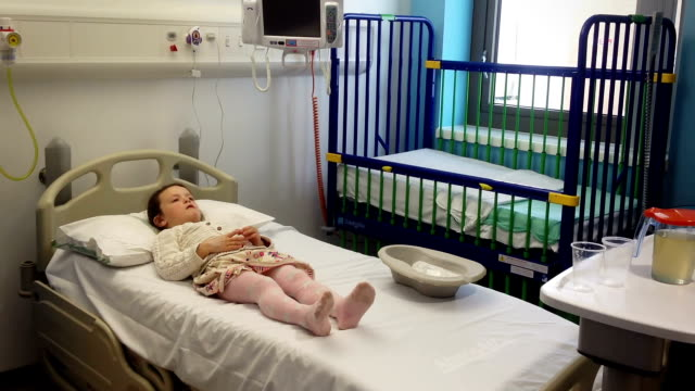 Little Girl In A Hospital Room Waiting Treatment A Little girl is waiting patiently for a doctor in a private hospital room. nhs stock videos & royalty-free footage