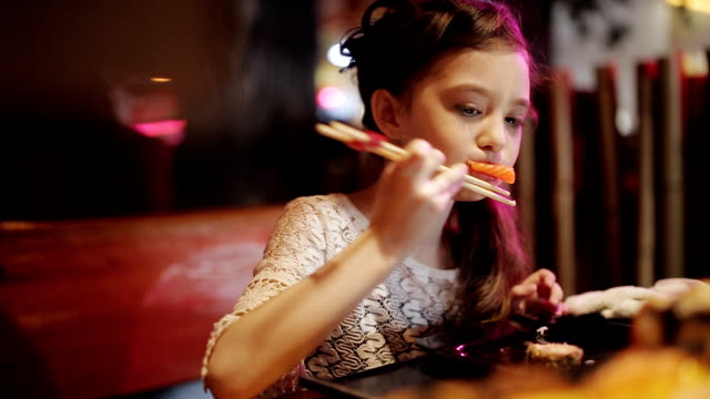 vídeos y material grabado en eventos de stock de niña en un intento de restaurante japonés del sushi rollos de palillos - sushi