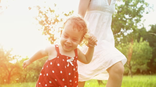 SLO MO TS Little girl in a red dotty dress running with her older sister in a white dress across a sunny meadow