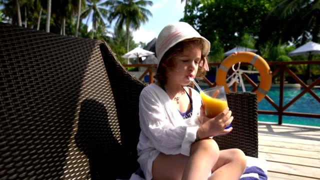 vídeos de stock e filmes b-roll de menina em um chapéu de palha beber sumo na piscina. - mulher natureza flores e piscina