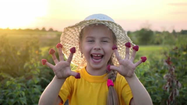Little girl in a straw hat laughs showing hands with raspberries on her fingers. Happy child with raspberries. Organic products. Healthy cheerful child. Vitamins for growth. Vegetarianism.