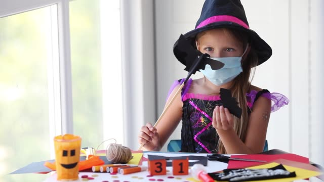 A little girl in a witch costume in a medical mask plays a bat with a craft. Halloween party with security measures for Covid-19