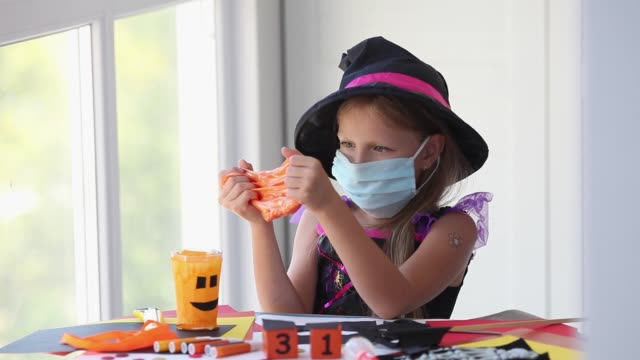 A little girl in a witch costume in a medical mask plays with a slime. Halloween party with security measures for Covid-19