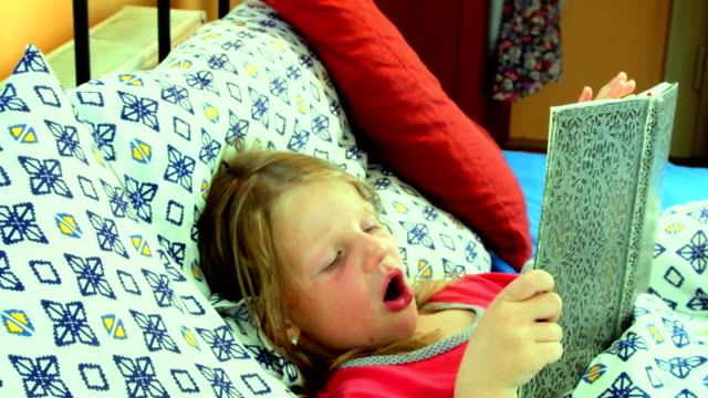 Little girl in bed. Girl looks at an old father diary. Small girl looks at an old book in bed. Zoom camera movement. Family concept video