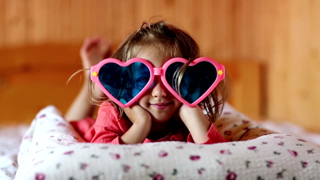 Little girl in big glasses in the shape of hearts lies on the bed video