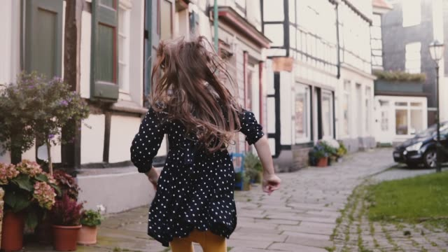 little girl in black dress running on old road. back view slow motion. half-timbered houses. happy carefree childhood - сбежавший из дома стоковые видео и кадры b-roll