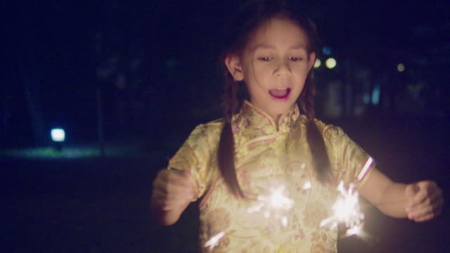 Little girl in Chinese dress with a sparkler at night. Mixed race girl dancing with sparkler in Chinese New Year Festival at night. Bangkok, Thailand. chinese new year stock videos & royalty-free footage