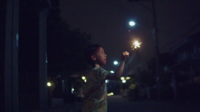 dziewczynka w chińskiej sukience z iskierką w nocy. - chinese new year filmów i materiałów b-roll