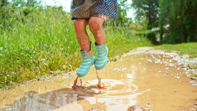 SLO MO Little girl in dotty dress and rainboots covered in mud from jumping in a muddy puddle