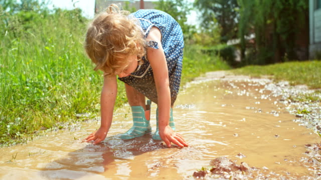 SLO MO Little girl in dotty dress covered in mud from head to toe smiling into the camera