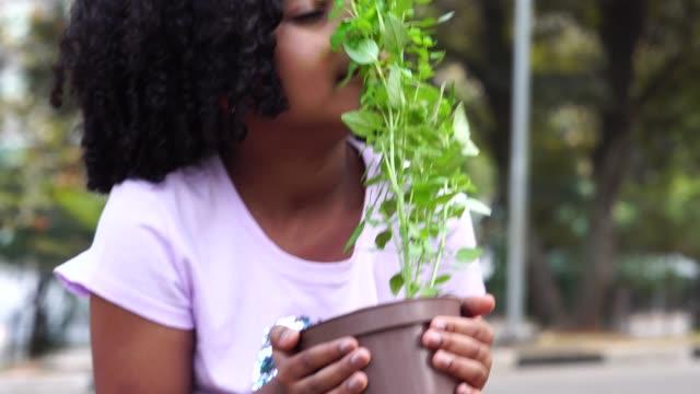 Niña en el jardín, que huele a planta fresca - vídeo