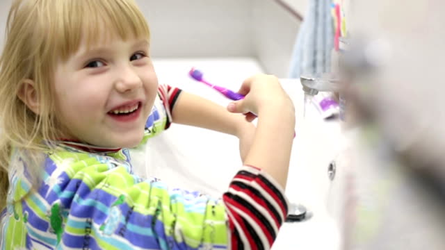 Little girl in green pajamas in the bathroom. video