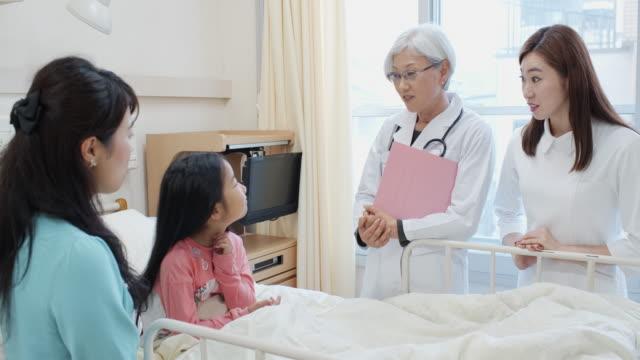 小児科医に囲まれた病院のベッドの小さな女の子、母と看護師 - 回復点の映像素材/bロール