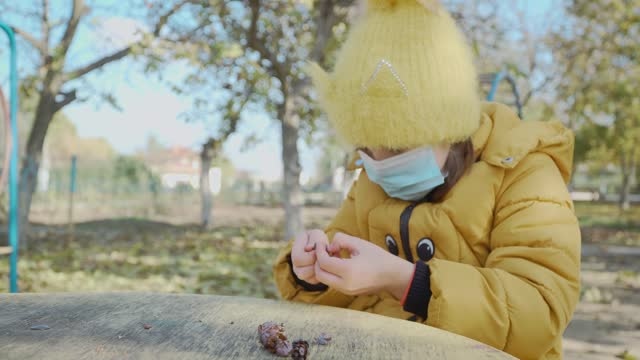 Little girl in medical face mask playing alone on children playground and holding in her hand some fruit