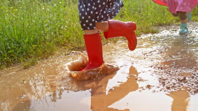 vídeos de stock e filmes b-roll de slo mo little girl in red rain boots running across a muddy puddle - poça