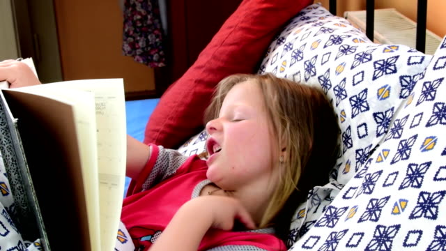 Little girl in the bed. Girl looks at an old father diary. Small girl looks at an old book in the bed. Family concept video